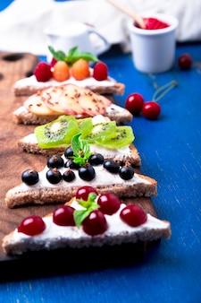 Pane tostato della frutta sul bordo di legno su blu rustico. colazione salutare. mangiare pulito. dieta fette di pane di grano con crema di formaggio e vari frutti, bacche, semi. vegetariano. vista dall'alto.