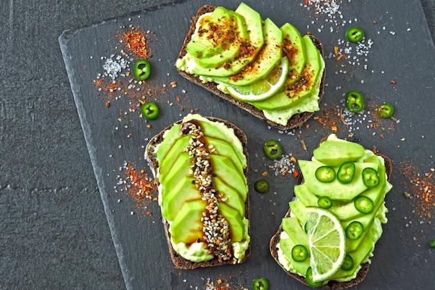 Pane tostato di avocado di segale con peperoncino e lime su un tagliere di pietra. toast avocado sano. vista dall'alto. disteso.