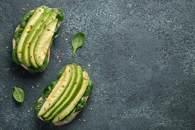 Pane tostato di due ciabatta con avocado affettato.