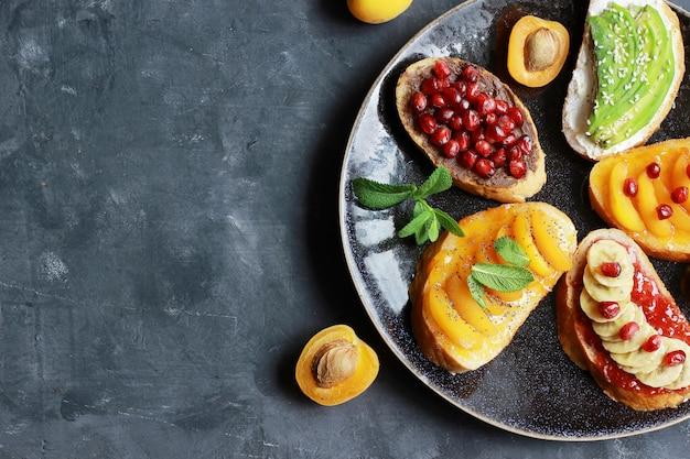 Pane tostato dolce con marmellata e vari frutti albicocche, banane, melograni e avocado sullo sfondo scuro copia spazio vista dall'alto.