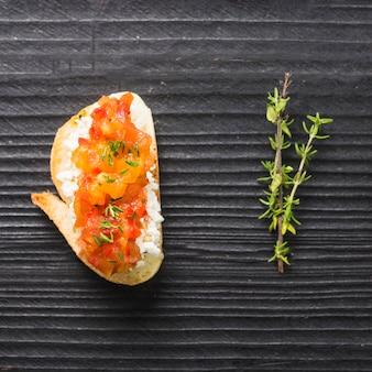 Pane tostato sano con formaggio e pomodori e timo sul contesto di legno della plancia