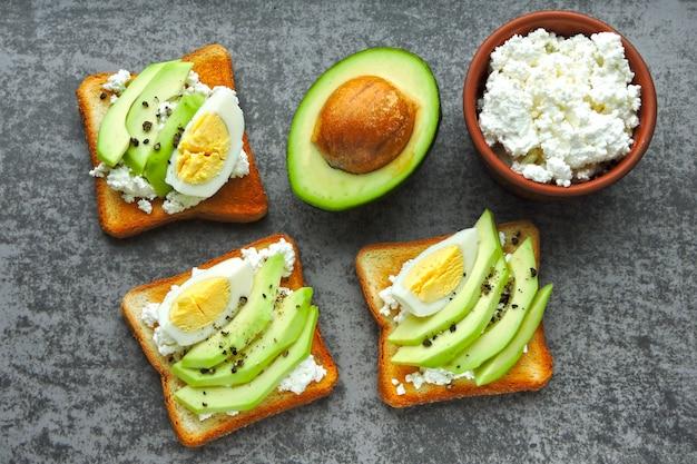 Pane tostato sano dell'avocado della ricotta con l'uovo.