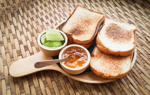 Pane tostato servito sul vassoio in legno con marmellata dolce e colazione fatta in casa lime