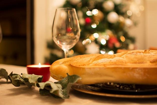 Pane, un bicchiere di vino, eucalipto secco, una candela