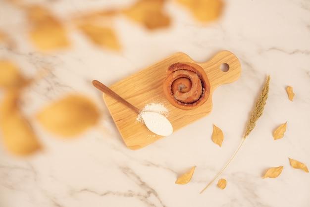 Panetteria fresca, panino alla cannella fresca con cucchiaio pieno di farina su tavola di legno sulla superficie di marmo bianco. gustoso dessert delizioso, colazione francese. vista dall'alto