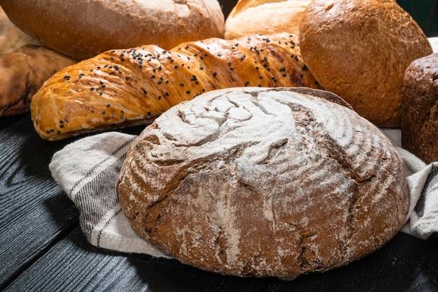 Panetteria multipla del pane boule sulla tavola di legno del tessuto