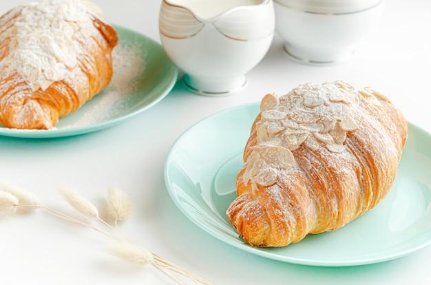 Panetteria per la colazione, cornetto con zucchero a velo e scaglie di mandorle su sfondo bianco. avvicinamento.