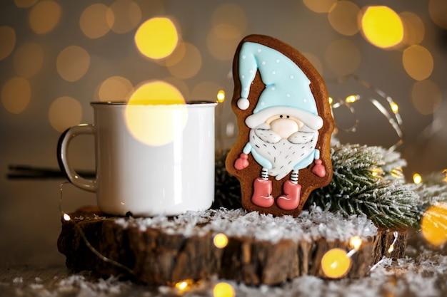 Panetteria tradizionale per vacanze. pan di zenzero piccolo gnomo da favola in una decorazione accogliente con luci ghirlanda e tazza di caffè caldo