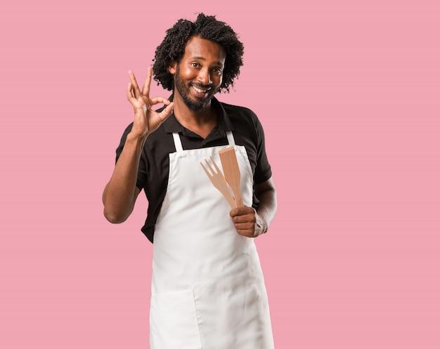 Panettiere afroamericano bello allegro e sicuro facendo gesto giusto, eccitato e urlando, concetto di approvazione e successo