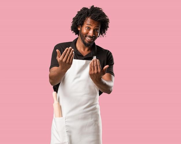 Panettiere afroamericano bello che invita a venire, sicuro e sorridente che fa un gesto con la mano