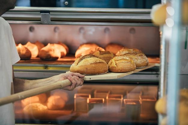 Panettiere che produce pane ad un forno. concetto di panetteria.