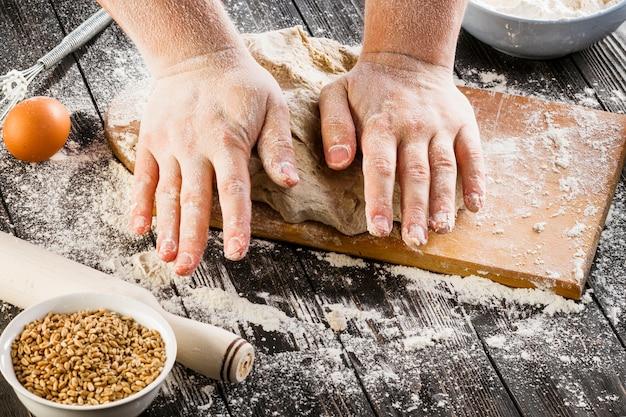 Panettiere che produce pasta di pane con farina di frumento