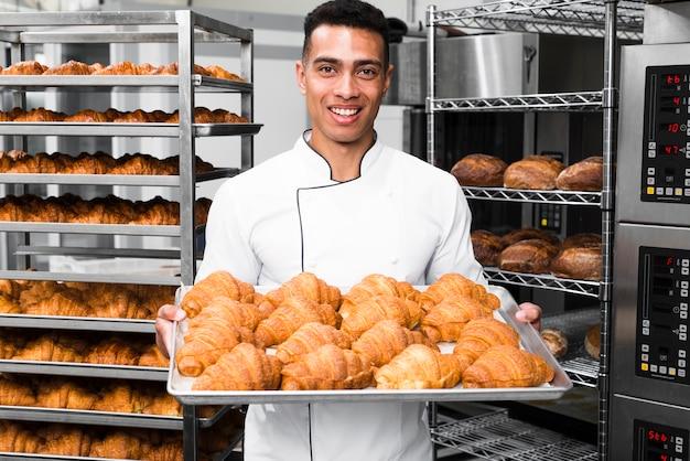Panettiere che sorride alla macchina fotografica che tiene vassoio di croissant in una cucina commerciale