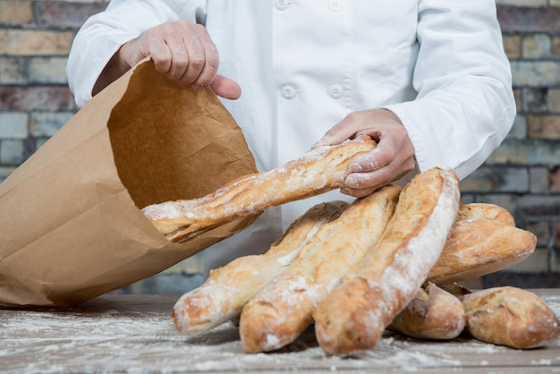 Panettiere che tiene le baguette francesi tradizionali del pane