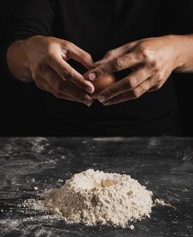 Panettiere del primo piano che prepara rompere un uovo