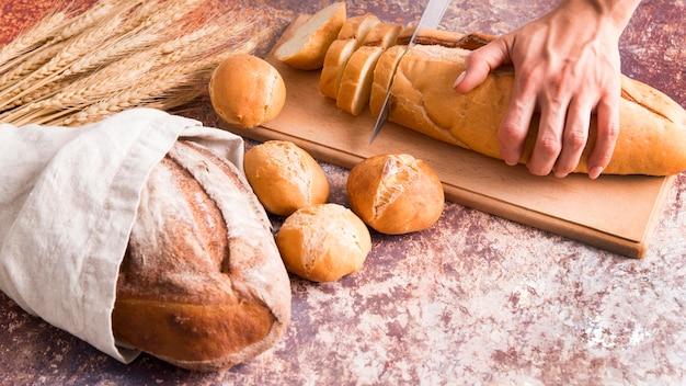Panettiere dell'angolo alto che affetta pagnotta di pane