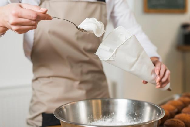 Panettiere femminile che riempie panna montata nel sacchetto di glassa bianco