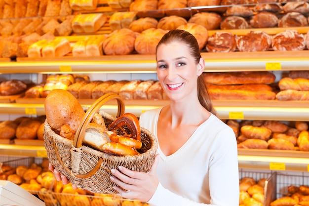 Panettiere femminile che vende pane nel suo forno