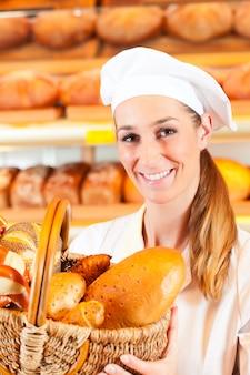 Panettiere femminile nel forno che vende pane dal cestino