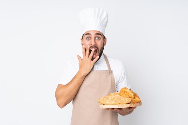 Panettiere maschio che tiene una tavola con parecchi pani isolati sulla parete bianca con espressione facciale di sorpresa