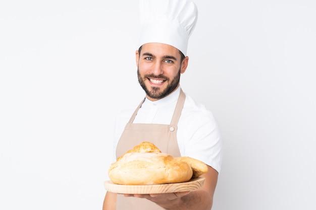 Panettiere maschio che tiene una tavola con parecchi pani su bianco