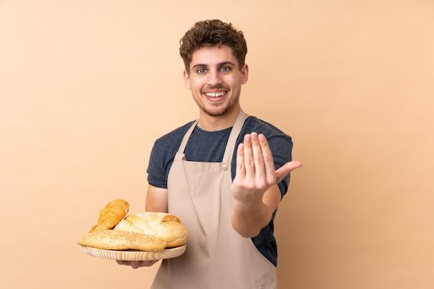 Panettiere maschio che tiene una tavola con parecchi pani sulla parete beige che invita a venire