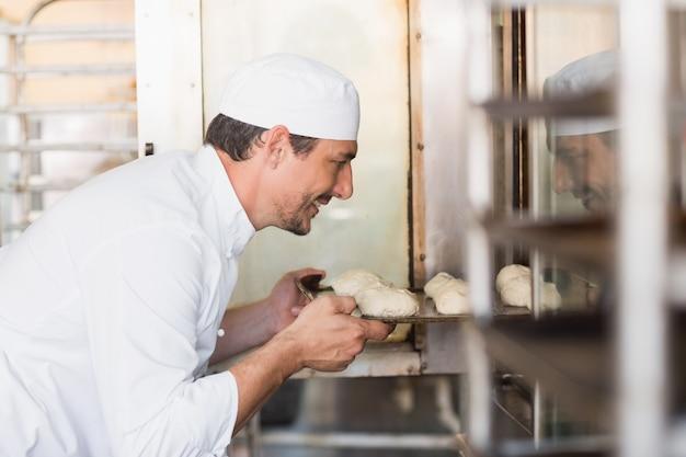 Panettiere sorridente che mette la pasta in forno nella cucina del forno