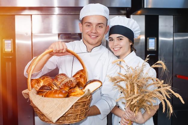 Panettieri ragazzo e ragazza con un cesto da forno e spighette
