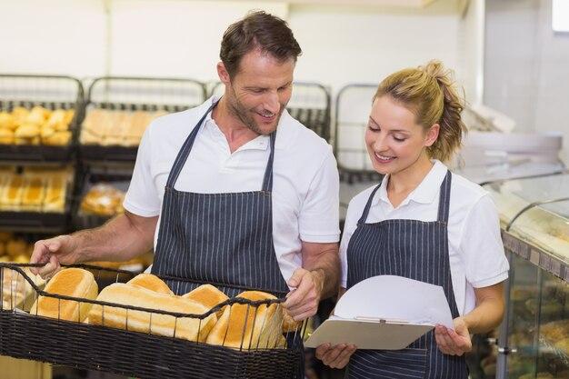 Panettieri sorridenti che esaminano blocco note e che tengono un canestro con pane