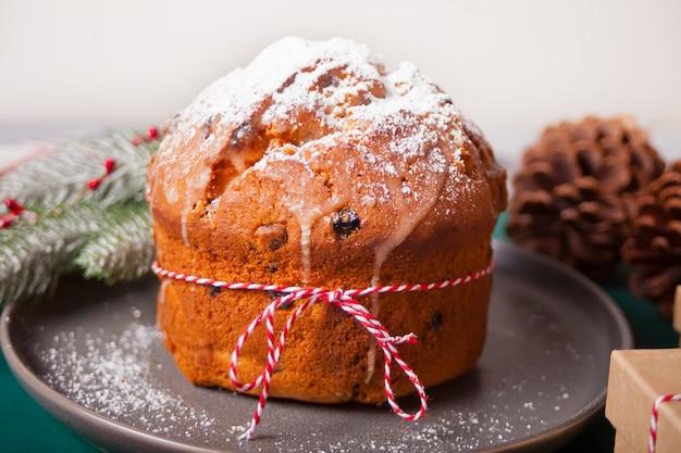 Panettone tradizionale natalizio con frutta e noci con decorazioni natalizie