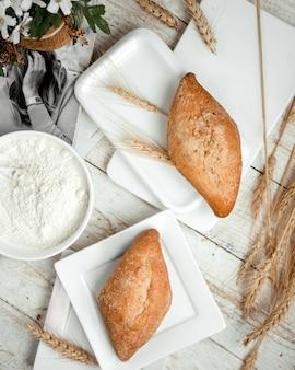 Panificio con panna acida e ramo di grano sul tavolo