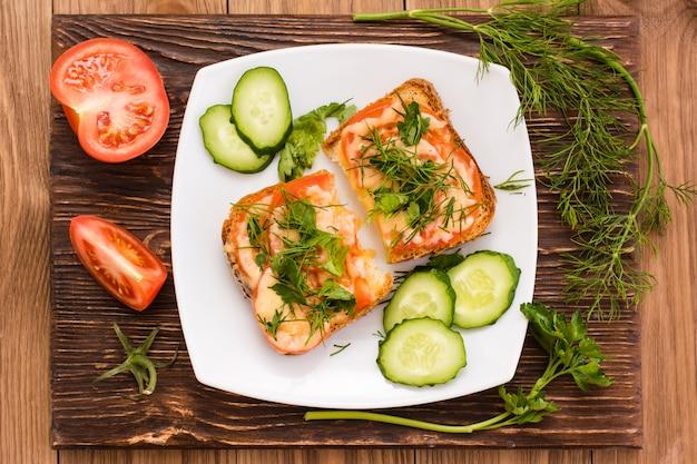 Panini al forno con pomodoro, formaggio e verdure e verdure a fette. vista dall'alto