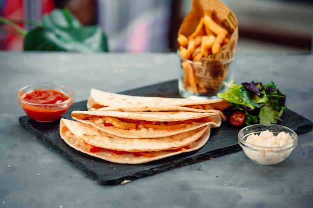 Panini al lavash con salsa di pomodoro, insalata verde e patatine fritte.