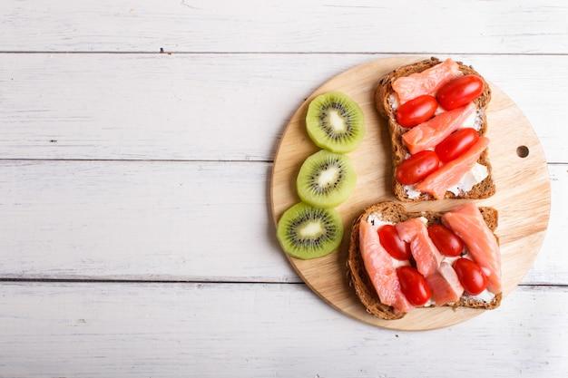 Panini al salmone affumicato con burro e pomodorini su fondo di legno bianco.
