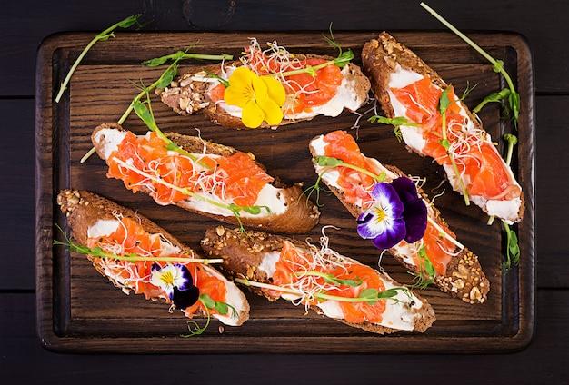 Panini al salmone con crema di formaggio e microgreen sul tavolo di legno. canape al salmone.
