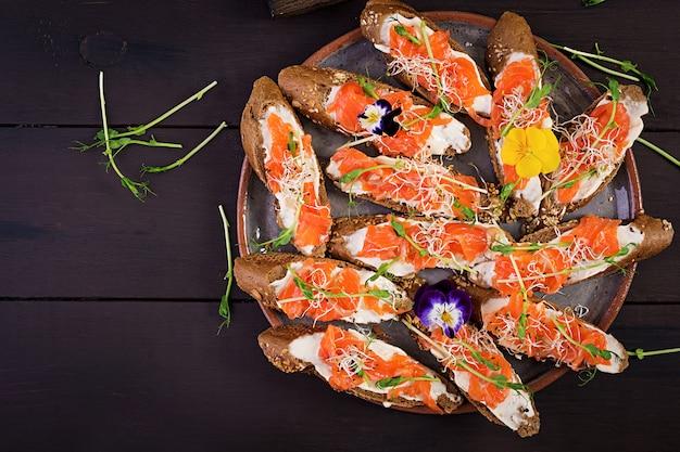 Panini al salmone con crema di formaggio e microgreen sul tavolo di legno