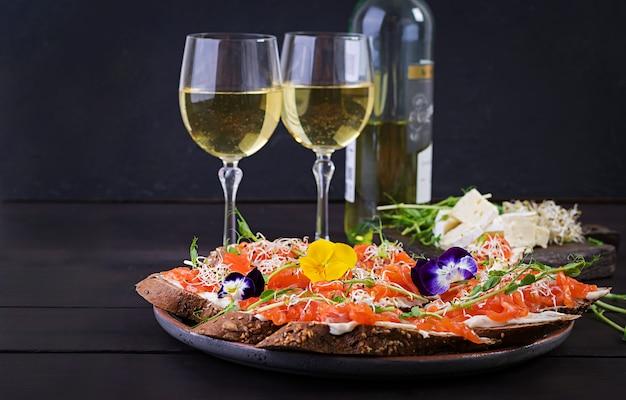 Panini al salmone con crema di formaggio e microgreen sul tavolo di legno.