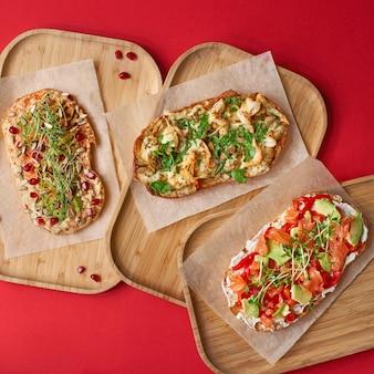 Panini aperti avocado e salmone, formaggio a pasta molle. panino fatto in casa con gamberi e funghi, con hummus, su tavola di legno. vista dall'alto, sandwich vicino