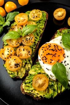 Panini aperti con guacamole di avocado, pomodorini gialli, uovo fritto e basilico su un piatto nero. avvicinamento.