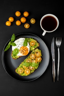 Panini aperti con guacamole di avocado, pomodorini gialli, uovo fritto e basilico su un piatto nero. vista dall'alto.