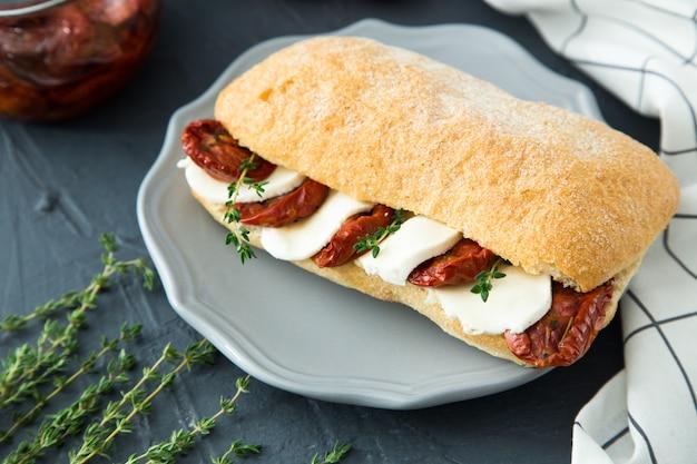 Panini assortiti panino caprese con mozzarella e pomodori secchi e ciabatta con prosciutto