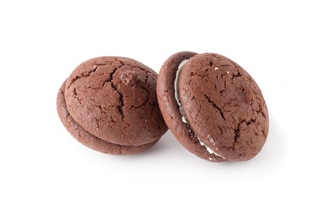 Panini biscotti al cioccolato e crema su un piatto bianco isolato su sfondo bianco