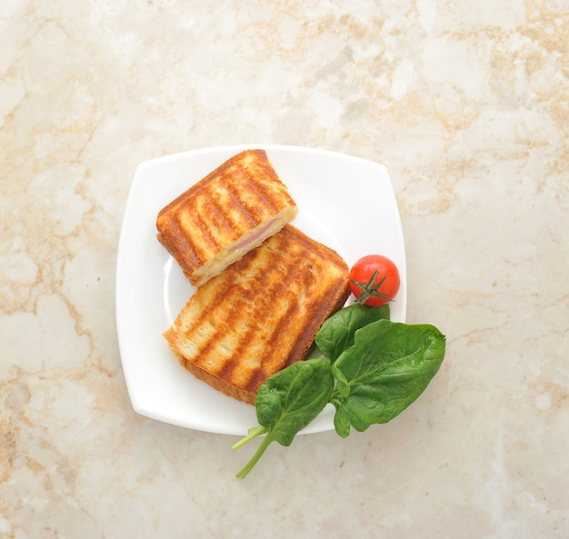 Panini caldi su un piatto con foglie di spinaci e pomodorini