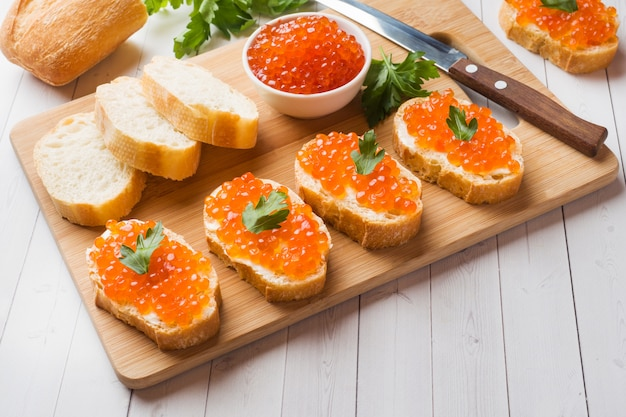 Panini con caviale di salmone rosso su una tavola di legno. piano tavolo bianco.