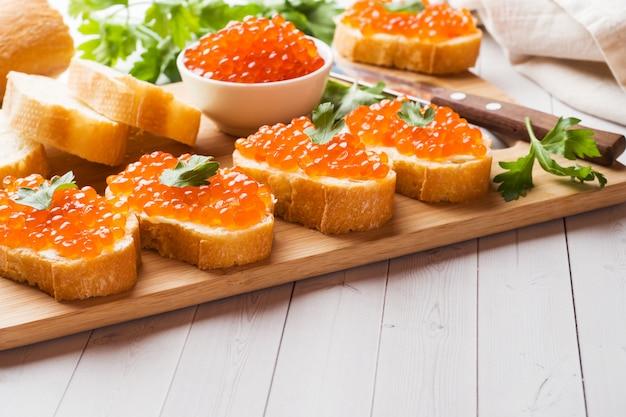 Panini con caviale di salmone rosso su una tavola di legno