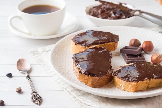 Panini con cioccolato e nocciole sparsi sul piatto. tazza di caffè sul tavolo.