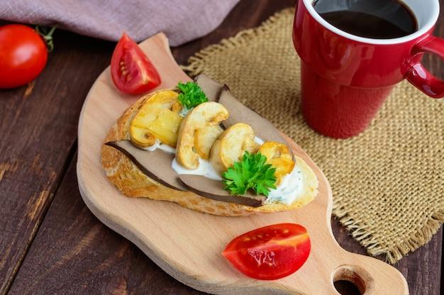 Panini con funghi, fegato di tacchino e salsa tartara su baguette croccanti e una tazza di caffè. colazione dietetica