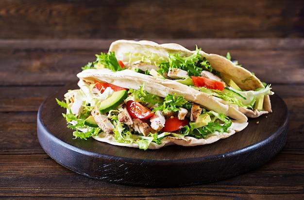 Panini con pane alla griglia con carne di pollo alla griglia, avocado, pomodori, cetrioli e lattuga serviti su legno