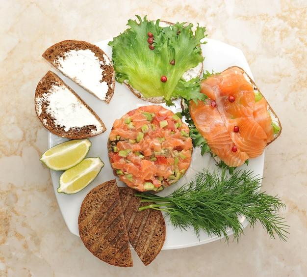 Panini con pesce rosso e tartaro di salmone su un piatto