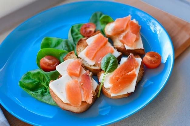 Panini con pesce rosso su un piatto blu. decorato con verdure